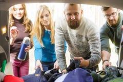 Groupe d'amis heureux prenant leurs sacs d'une voiture pour commencer une hausse Images libres de droits