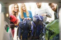 Groupe d'amis heureux prenant leurs sacs d'une voiture pour commencer une hausse Photo libre de droits