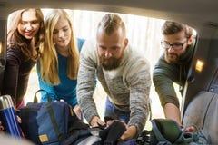 Groupe d'amis heureux prenant leurs sacs d'une voiture pour commencer une hausse Photos libres de droits