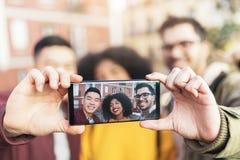 Groupe d'amis heureux prenant un selfie dans la rue Images stock