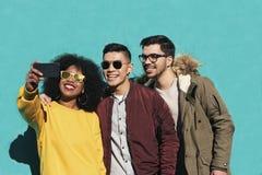 Groupe d'amis heureux prenant un selfie dans la rue Photographie stock libre de droits