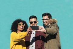 Groupe d'amis heureux prenant un selfie dans la rue Photos libres de droits