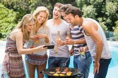 Groupe d'amis heureux regardant le téléphone portable Images libres de droits