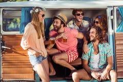 Groupe d'amis heureux s'asseyant en bière campervan et potable Photo stock