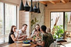 Groupe d'amis heureux s'asseyant et mangeant sur la cuisine Photo libre de droits