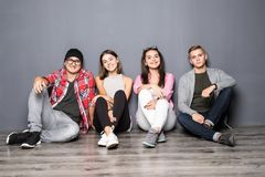 Groupe d'amis heureux s'asseyant sur le plancher à la maison Images stock