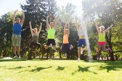 Groupe d'amis heureux sautant haut dehors Images libres de droits