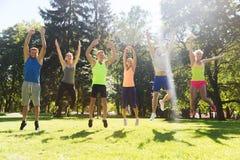 Groupe d'amis heureux sautant haut dehors Photographie stock