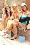 Groupe d'amis heureux se reposant après l'achat dans la ville Photographie stock
