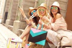 Groupe d'amis heureux se reposant après l'achat dans la ville Image libre de droits