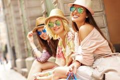 Groupe d'amis heureux se reposant après l'achat dans la ville Photos libres de droits