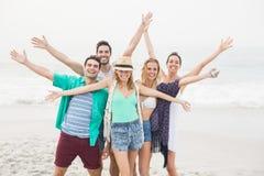 Groupe d'amis heureux se tenant sur la plage Images libres de droits