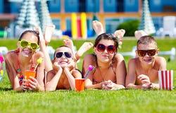 Groupe d'amis heureux sur la pelouse d'été Photographie stock