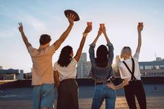 Groupe d'amis heureux sur le toit Photographie stock libre de droits