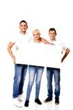 Groupe d'amis heureux tenant la bannière vide Image stock