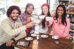 Groupe d'amis heureux tenant la tasse de café Photo stock