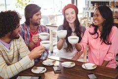 Groupe d'amis heureux tenant la tasse de café Image stock