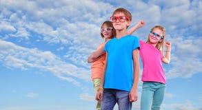 Groupe d'amis heureux utilisant des lunettes contre le ciel bleu Images stock