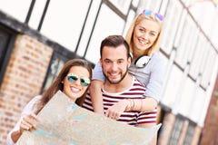 Groupe d'amis heureux visitant le pays avec la carte Photographie stock libre de droits