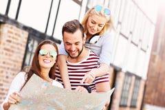 Groupe d'amis heureux visitant le pays avec la carte Photographie stock