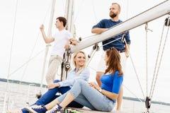 Groupe d'amis heureux voyageant sur un yacht Image stock