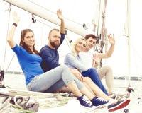 Groupe d'amis heureux voyageant sur un yacht, appréciant une bonne somme Image libre de droits