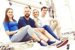 Groupe d'amis heureux voyageant sur un yacht, appréciant une bonne somme Photographie stock libre de droits