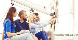 Groupe d'amis heureux voyageant sur un yacht, appréciant une bonne somme Image stock