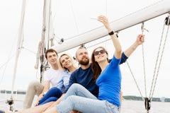 Groupe d'amis heureux voyageant sur un yacht et prenant le selfie T Photos stock