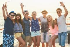 Groupe d'amis insouciants heureux traînant au bord de la mer ensoleillé d'été Photographie stock libre de droits