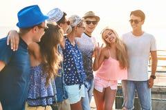 Groupe d'amis insouciants heureux traînant au bord de la mer ensoleillé d'été Image stock