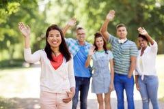 Groupe d'amis internationaux heureux ondulant des mains Photo stock