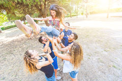 Groupe d'amis jetant une femme dans le ciel Photos libres de droits