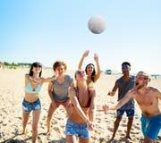 Groupe d'amis jouant à la volée de plage à la plage Image libre de droits