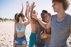 Groupe d'amis jouant à la volée de plage à la plage Photos stock