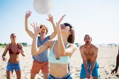 Groupe d'amis jouant à la volée de plage à la plage Images stock