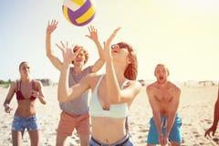 Groupe d'amis jouant à la volée de plage à la plage Photographie stock