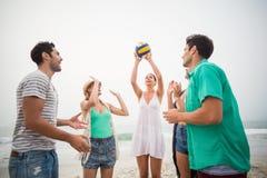 Groupe d'amis jouant avec du ballon de plage Images libres de droits