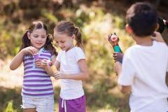 Groupe d'amis jouant avec la baguette magique de bulle Image stock