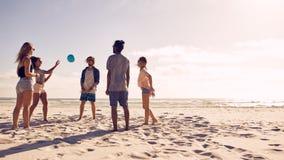 Groupe d'amis jouant avec la boule à la plage Images libres de droits