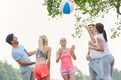 Groupe d'amis jouant avec la boule Images libres de droits