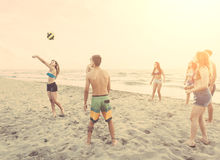 Groupe d'amis jouant avec la boule sur la plage Photos stock