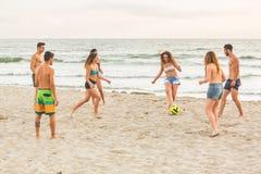Groupe d'amis jouant avec la boule sur la plage Photo stock