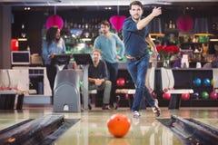 Groupe d'amis jouant dans le bowling Photos stock