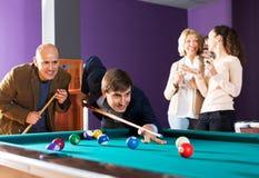 Groupe d'amis jouant des billards Image stock