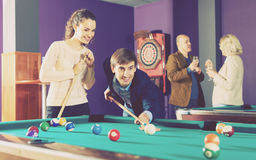 Groupe d'amis jouant des billards Photo stock