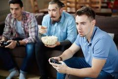 Groupe d'amis jouant des jeux vidéo sur le divan Photo libre de droits