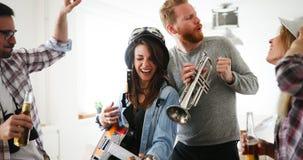 Groupe d'amis jouant la guitare et faisant la fête à la maison Image libre de droits