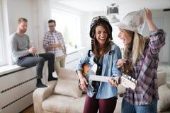 Groupe d'amis jouant la guitare et faisant la fête à la maison Image stock