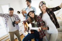 Groupe d'amis jouant la guitare et faisant la f?te ? la maison image libre de droits